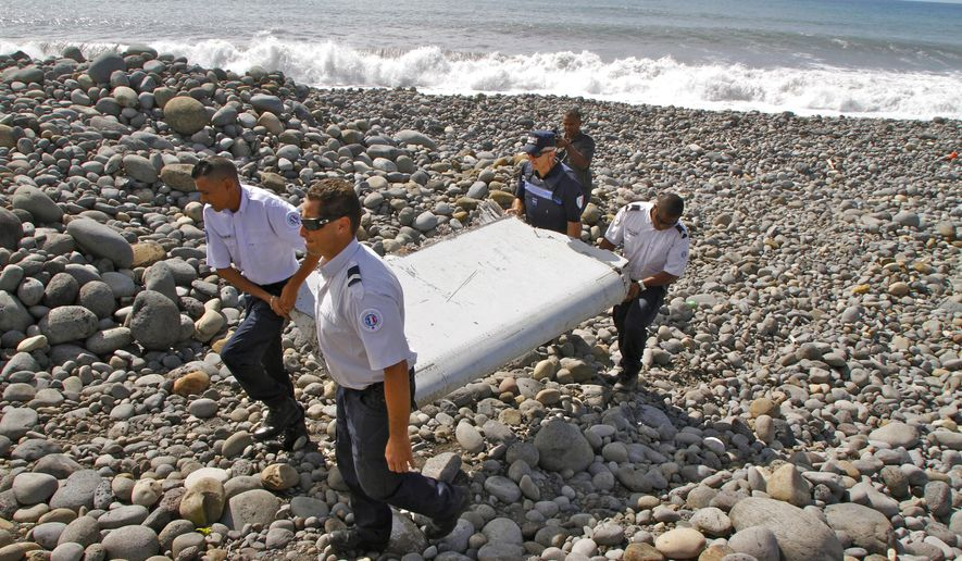 "FILE - In this July 29, 2015, file photo, French police officers carry a piece of debris from a plane known as a ""flaperon"" on the shore of Saint-Andre, Reunion Island. While search crews spent years trawling in futility through a remote patch of the Indian Ocean for the missing Malaysia Airlines Flight 370, people wandering along beaches on the other side of the ocean began spotting debris that washed ashore. Those pieces provided key information and raised questions whether Malaysia, Australia and China - who funded the hunt for the underwater wreckage - missed key opportunities by failing to organize coastal searches for plane parts. (AP Photo/Lucas Marie, File)"