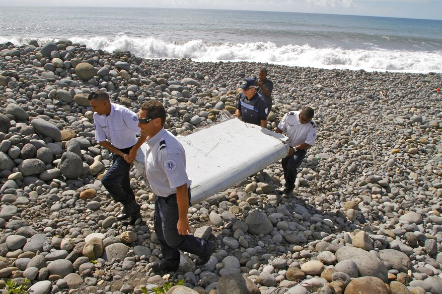 """FILE - In this July 29, 2015, file photo, French police officers carry a piece of debris from a plane known as a """"flaperon"""" on the shore of Saint-Andre, Reunion Island. While search crews spent years trawling in futility through a remote patch of the Indian Ocean for the missing Malaysia Airlines Flight 370, people wandering along beaches on the other side of the ocean began spotting debris that washed ashore. Those pieces provided key information and raised questions whether Malaysia, Australia and China - who funded the hunt for the underwater wreckage - missed key opportunities by failing to organize coastal searches for plane parts. (AP Photo/Lucas Marie, File)"""