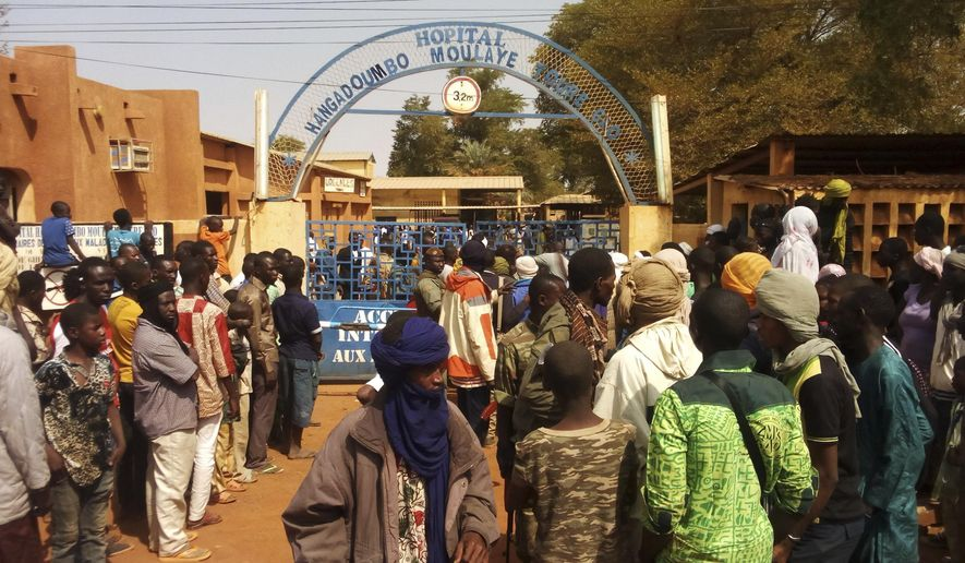 People gather outside a hospital were injured were taken after an explosion at the Joint Operational Mechanism base in Gao, Mali, Wednesday, Jan. 18, 2017. A suicide bomber in an explosives-laden vehicle attacked a camp in northern Mali on Wednesday, killing more than 50 people and wounding more than 100 soldiers and former fighters now trying to stabilize the region. (AP Photo/Yacouba Cisse)