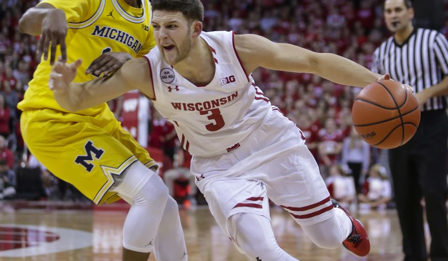 Wisconsin's Zak Showalter (3) drives on Michigan's Muhammad-Ali Abdur-Rahkman (12) during the second half of an NCAA college basketball game Tuesday, Jan. 17, 2017, in Madison, Wis. Wisconsin won 68-64. (AP Photo/Andy Manis)
