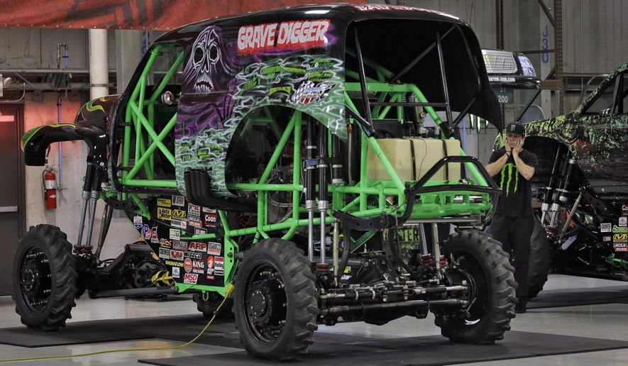"FILE - In this Nov. 25, 2014, file photo, Coty Saucier, far right, covers his ears as the monster truck ""Grave Digger"" gets its engine started at Feld Entertainment in Ellenton, Fla. Grave Digger driver Dennis Anderson was hurt in a crash at ""Monster Jam"" in Tampa, Fla. on Saturday, Jan. 14, 2017. (AP Photo/Chris O'Meara, File)"