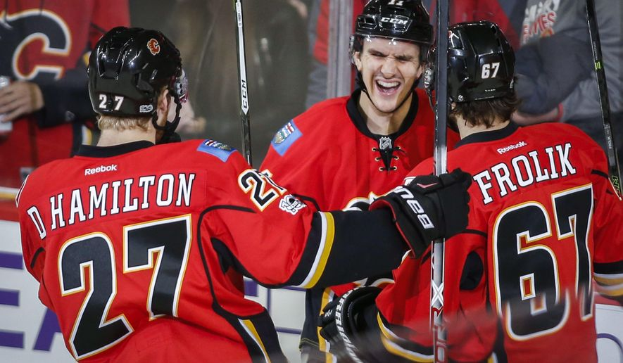 Calgary Flames' Mikael Backlund, center, from Sweden, celebrates his first goal with teammates during second period NHL hockey action in Calgary, Tuesday, Jan. 17, 2017. (Jeff McIntosh/The Canadian Press via AP)