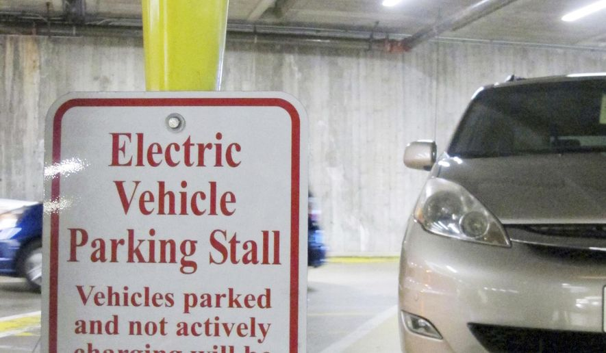 An electric vehicle charging station awaits a vehicle in the parking lot at the Hawaii State Legislature on Wednesday, Jan. 18, 2017 in Honolulu. Renewable energy advocates in Hawaii are pushing a bill to urge the transportation sector to get all its energy from renewable sources in 2045. (AP Photo/Cathy Bussewitz)