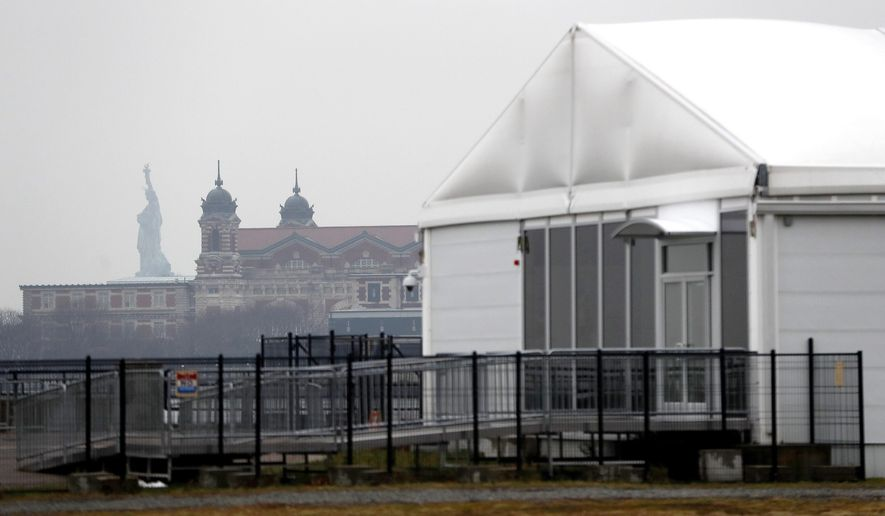 The Statue of Liberty, top left, and Ellis Island, center, give backdrop to a tent used as a security screening area for passengers before boarding ferries that take them to the landmarks, Tuesday, Jan. 17, 2017, in Jersey City, N.J. National Park Service spokesman Jerry Willis said there was bowing visible Tuesday in the tent-like structure. The center features airport-style X-ray screening. Visitors in New Jersey trying to visit the statue or island are being ferried to Lower Manhattan, where they can be screened at a security facility in New York City's Battery Park. Officials are trying to come up with a contingency for visitors if the center must remain closed. (AP Photo/Julio Cortez)