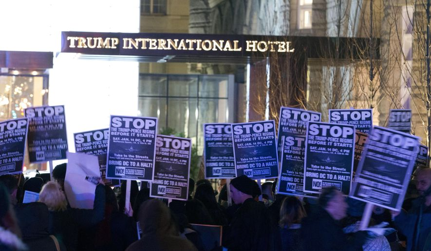 Demonstrators protest outside of the Trump Hotel during a march in downtown Washington in opposition of President-elect Donald Trump, Sunday, Jan. 15, 2017. ( AP Photo/Jose Luis Magana)