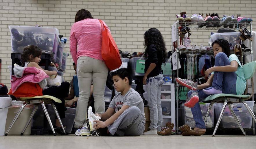 FILE - In this Nov. 13, 2016, file photo, Central American migrants newly released after processing by the U.S. Customs and Border Patrol are fitted for shoes at the Sacred Heart Community Center in the Rio Grande Valley border city of McAllen, Texas. Central Americans attempting to enter the United States illegally on the country's border with Mexico helped drive a 15 percent increase in immigration arrests during the 2016 fiscal year, according to U.S. Department of Homeland Security figures released Friday, Dec. 30. 2016. (AP Photo/Eric Gay, File)