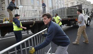 Workers unload barricades before placing them along Pennsylvania Avenue in Washington as security tightens ahead of the presidential inauguration. (Associated Press)