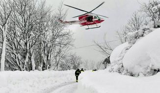 An Italian firefighters helicopter flies during rescue operations in the area where an hotel was hit by an avalanche in Farindola, Italy, early Thursday, Jan. 19, 2017. A hotel in the mountainous region hit again by quakes has been covered by an avalanche, with reports of dead. Italian media say the avalanche covered the three-story hotel in the central region of Abruzzo, on Wednesday evening. (Matteo Guidelli/ANSA via AP)