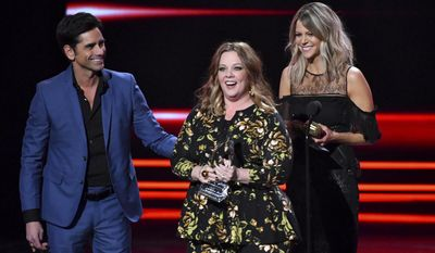 Melissa McCarthy, center, accepts the award for favorite comedic movie actress from John Stamos, left, and Kaitlin Olson, right, at the People's Choice Awards at the Microsoft Theater on Wednesday, Jan. 18, 2017, in Los Angeles. (Photo by Vince Bucci/Invision/AP)