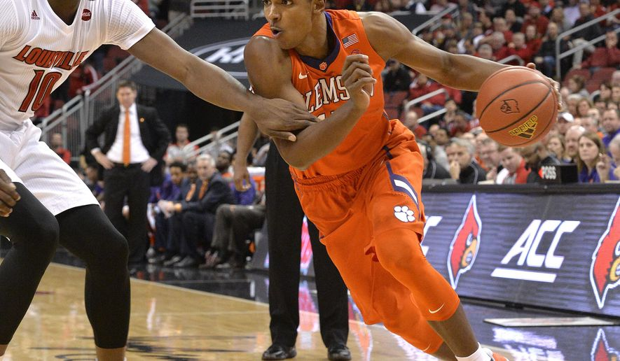 Clemson's Donte Grantham (15) attempts to drive past the defense of Louisville's Jaylen Johnson (10) during the first half of an NCAA college basketball game, Thursday, Jan. 19, 2017, in Louisville, Ky. (AP Photo/Timothy D. Easley)