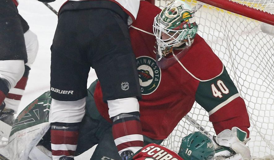 Minnesota Wild goalie Devan Dubnyk, right, topples into the net as Arizona Coyotes' Jamie McGinn, left, skates into him during the first period of an NHL hockey game Thursday, Jan. 19, 2017, in St. Paul, Minn. (AP Photo/Jim Mone)