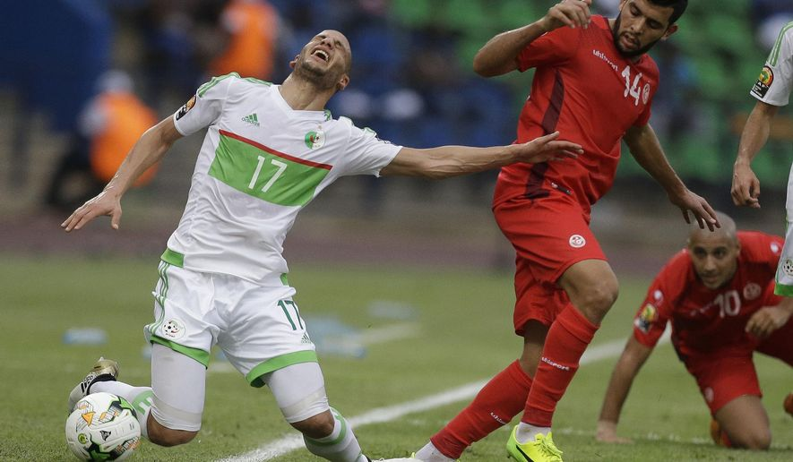 Algeria's, Adlane Guedioura, left, is challenged by Tunisia's, Mohamed Amine Ben Amor, during the African Cup of Nations Group B soccer match between Algeria and Tunisia at, Stade de Franceville Stadium, Gabon Thursday Jan. 19, 2017. (AP Photo/Sunday Alamba)