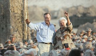 FILE - In this Nov. 22, 1990, file photo, President George H.W. Bush and first lady Barbara Bush wave to U.S. Marines during a Thanksgiving visit at the desert encampment in Saudi Arabia. Both Bushes have been hospitalized this week in Houston, where the former president is being treated for pneumonia and his wife for bronchitis. (AP Photo/Scott Applewhite, File)