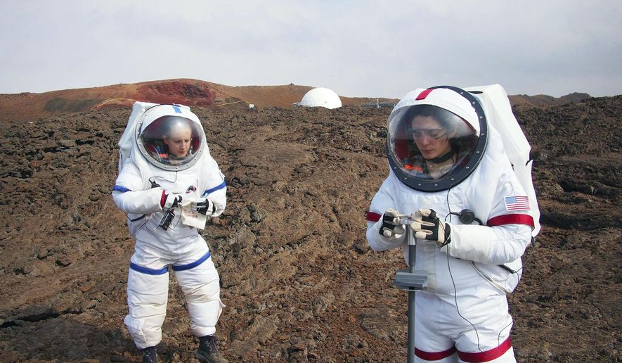 In this May 23, 2014 photo provided by the University of Hawaii, Lucie Poulet, right, uses a geotechnical tool while Annie Caraccio records the data during a previous study outside the domed structure that will house six researchers for eight months in an environment meant to simulate an expedition to Mars, on Mauna Loa on the Big Island of Hawaii. The group will enter the dome Thursday, Jan. 19, 2017, and spend eight months together in the 1,200-square-foot research facility in a study called Hawaii Space Exploration Analog and Simulation (HI-SEAS). They will have no physical contact with any humans outside their group, experience a 20-minute delay in communications and are required to wear space suits whenever they leave the compound. (Ross Lockwood/University of Hawaii via AP)