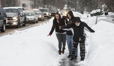 Brittany Silva, 25, Sheena Hutson, 30, and Stephanie Jones, 25, slide their way down the sidewalk on Walnut at Eighth Avenue as traffic backs up on the icy surfaces, Wednesday, Jan. 18, 2017, in Spokane, Wash. (Dan Pelle/The Spokesman-Review via AP)