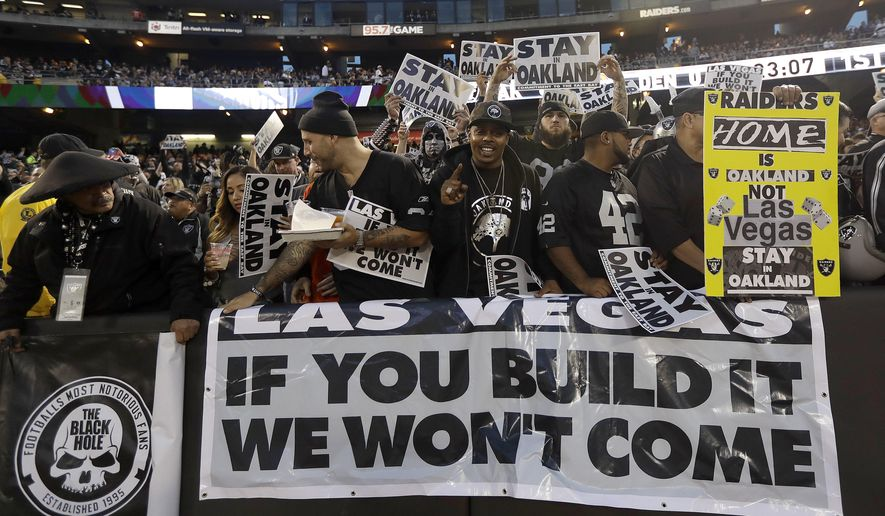 FILE - In this Nov. 6, 2016, file photo, Oakland Raiders fans hold up signs about the team's possible move to Las Vegas during an NFL football game between the Raiders and the Denver Broncos in Oakland, Calif. The Raiders have filed paperwork to move to Las Vegas. Clark County Commission Chairman Steve Sisolak told The Associated Press on Thursday, Jan. 19, 2017,  that he spoke with the Raiders. (AP Photo/Marcio Jose Sanchez, File)