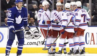 New York Rangers players celebrate a goal against the Toronto Maple Leafs as Maple Leafs' left wing James van Riemsdyk (25) looks on during the second period of an NHL hockey game, Thursday, Jan. 19, 2017 in Toronto. (Frank Gunn/The Canadian Press via AP)
