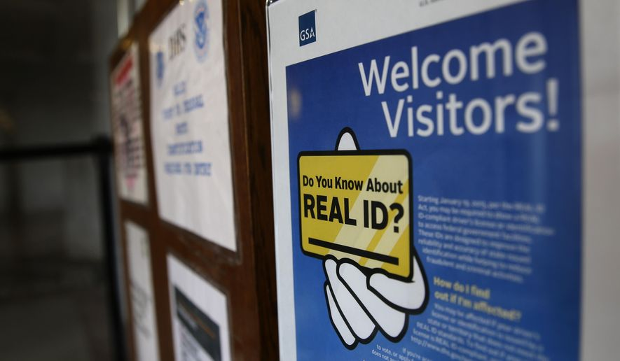 FILE - In this photo taken April 6, 2016, a sign at the federal courthouse in Tacoma, Wash., is shown to inform visitors of the federal government's REAL ID act, which requires state driver's licenses and ID cards to have security enhancements and be issued to people who can prove they're legally in the United States. Lawmakers in Washington state are now trying to bring the state in compliance with the law, and if state-issued identification cards and licenses are not changed, residents may have to produce additional forms of ID when boarding domestic flights at U.S. airports beginning in January, 2018. (AP Photo/Ted S. Warren, file)