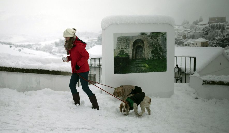 A woman walks with her dogs through a street after snowfall in the city of Ronda, southern Spain, Thursday, Jan. 19, 2017. The schools of Ronda, one of the most historical towns of Andalusia, suspended their classes Thursday and traffic has been interrupted on several highways due to the intense snowfall that has fallen during the night. A cold spell has reached Europe with temperatures plummeting far below zero. (AP Photo/Javier Gonzalez)