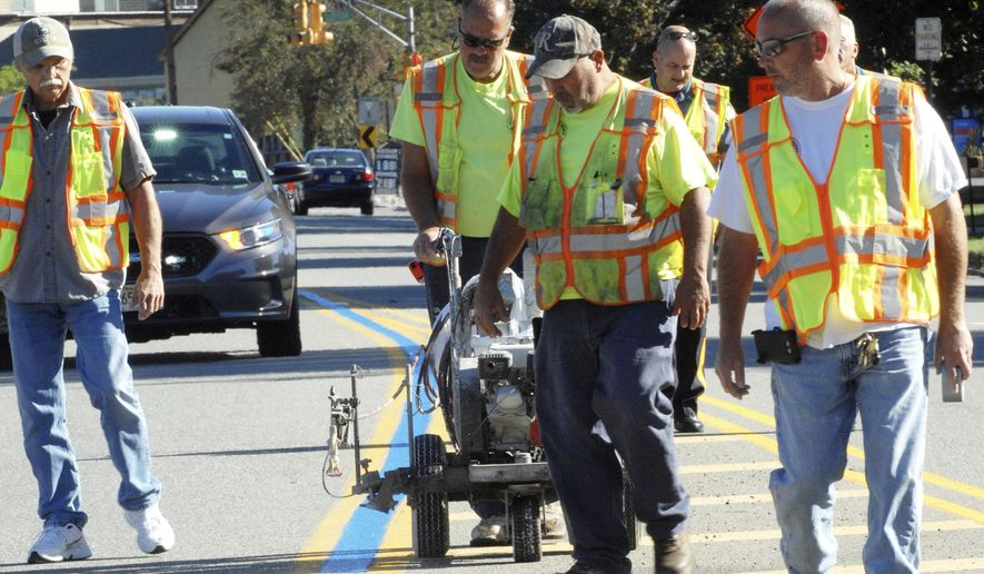 In this Sept. 12, 2016 photo, Wayne, N.J., Department of Public Works employees paint blue line in middle of solid yellow lines on a roadway. Blue lines have been appearing on streets in New Jersey and many other states in recent months to show support for law enforcement. (Demitrius Balevski/The Record via AP)