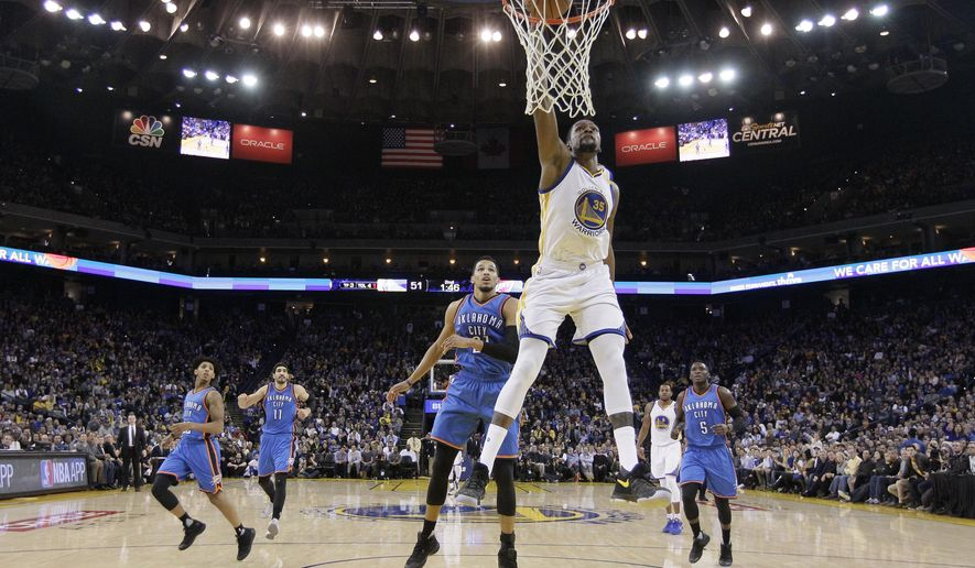 Golden State Warriors' Kevin Durant (35) drives for a dunk attempt past Oklahoma City Thunder's Andre Roberson, center left, during the first half of an NBA basketball game Wednesday, Jan. 18, 2017, in Oakland, Calif. (AP Photo/Marcio Jose Sanchez)