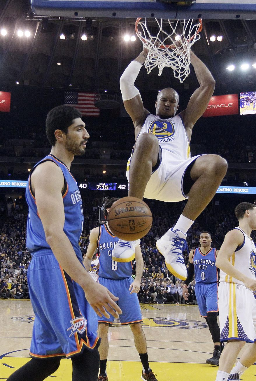 Golden State Warriors' David West (3) dunks next to Oklahoma City Thunder's Enes Kanter, left, during the first half of an NBA basketball game Wednesday, Jan. 18, 2017, in Oakland, Calif. (AP Photo/Marcio Jose Sanchez)
