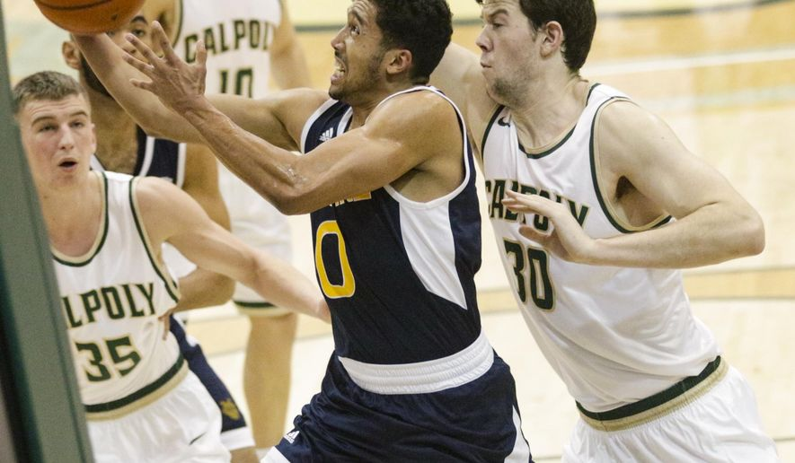 UC Irvine's Jaron Martin (00) drives against Cal Poly's Jakkub Niziol (35) and Hank Hollingsworth (30) in an NCAA college basketball game in San Luis Obispo, Calif., Wednesday, Jan. 18, 2017. (David Middlecamp/The Tribune (of San Luis Obispo) via AP)