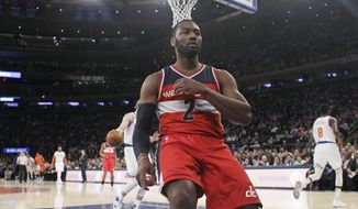 Washington Wizards' John Wall (2) reacts after a dunk in front of New York Knicks' Justin Holiday (8) during the first half of an NBA basketball game Thursday, Jan. 19, 2017, in New York. (AP Photo/Frank Franklin II)