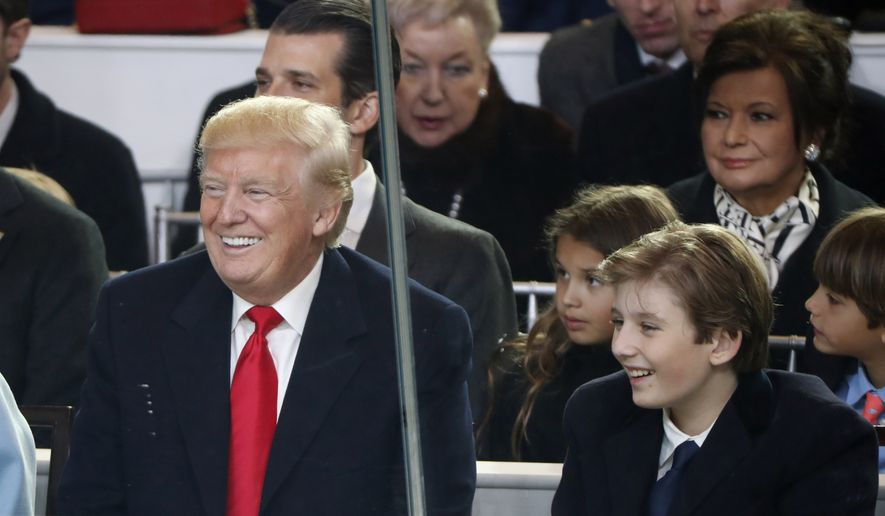 President Donald Trump smiles with his son Barron as they view the 58th Presidential Inauguration parade for President Donald Trump in Washington. Friday, Jan. 20, 2017 (AP Photo/Pablo Martinez Monsivais)