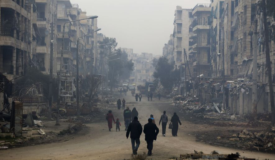 Residents walk through the destruction of the once rebel-held Salaheddine neighborhood in the eastern Aleppo, Syria, Friday, Jan. 20, 2017. Last month, government forces captured all parts of eastern Aleppo, brining Syria's largest city to full control of Syrian authorities for the first time since July 2012. (AP Photo/Hassan Ammar)