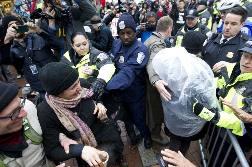 Police officers push back demonstrators attempting to block people entering a security checkpoint, Friday, Jan. 20, 2017, ahead of President-elect Donald Trump's inauguration in Washington. ( AP Photo/Jose Luis Magana)