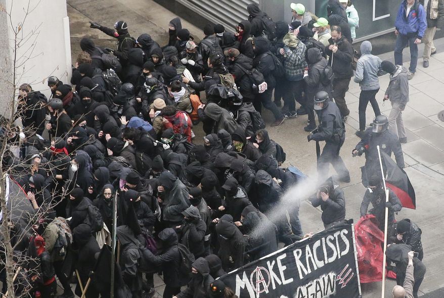 Police use pepper spray on protesters in Washington, Friday, Jan. 20, 2017, in a chaotic confrontation blocks from Donald Trump's inauguration as protesters registered their rage against the new president. (AP Photo/Mark Tenally)