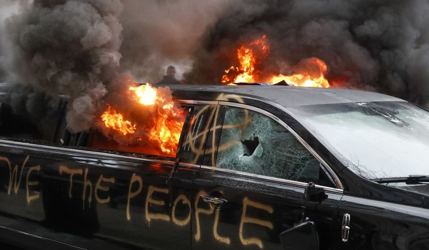 A parked limousine burns during a demonstration after the inauguration of President Donald Trump, Friday, Jan. 20, 2017, in Washington. (AP Photo/John Minchillo)