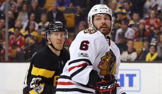 Chicago Blackhawks defenseman Michal Kempny (6) and Boston Bruins' Riley Nash watch the puck during the second period of an NHL hockey game in Boston on Friday, Jan. 20, 2017. (AP Photo/Winslow Townson)