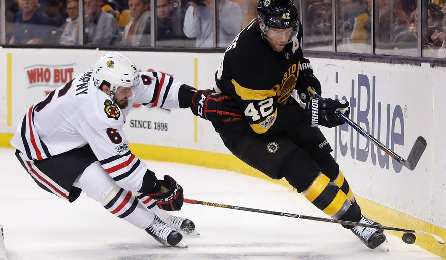 Chicago Blackhawks defenseman Michal Kempny (6) tries to knock the puck away from Boston Bruins' David Backes during the second period of an NHL hockey game in Boston Friday, Jan. 20, 2017. (AP Photo/Winslow Townson)