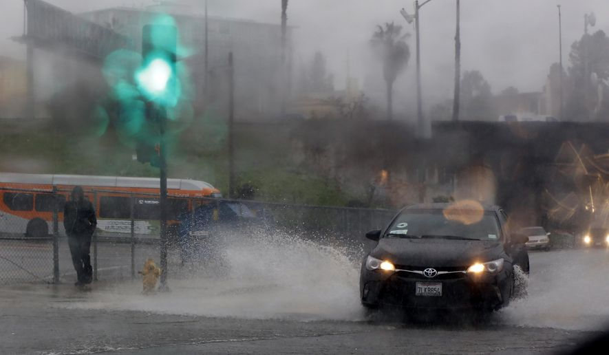 Raindrops bead upon a windshield as a pedestrian walks through rain in downtown Los Angeles, Friday, Jan. 20, 2017. The second in a trio of storms has arrived in California. Rain, heavy at times, is overspreading the state early Friday and a flash flood warning has been issued for southeastern Sonoma County. (AP Photo/Damian Dovarganes)