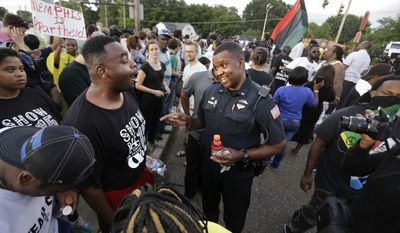 FILE - In this Aug. 15, 2016 file photo, Memphis police department Lieutenant A. Gardner, center right, talks with a protester, Antonio Blair, center left, during a protest at  Graceland's Elvis Candelight Vigil in Memphis, Tenn. Five people have filed a federal civil rights lawsuit against the city of Memphis and Elvis Presley's Graceland, saying they were discriminated against at a protest by a coalition associated with the Black Lives Matter movement during the annual vigil commemorating the singer's death.Graceland owner, Elvis Presley Enterprises, and the city are named in the complaint filed Wednesday, Jan. 18, 2017 in federal court. (Nikki Boertman/The Commercial Appeal via AP)