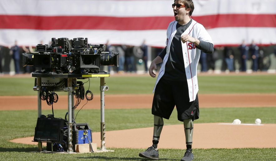 "FILE - In this April 18, 2016 file photo, Boston Marathon bombing survivor Jeff Bauman reacts beside a cluster of movie cameras after throwing out a pitch before an MLB baseball game between the Boston Red Sox and the Toronto Blue Jays at Fenway Park in Boston. Bauman was at the park with actor Jake Gyllenhaal filming a scene for the movie, ""Stronger."" Hollywood films that portray the bombings have not yet disclosed how much they've sought or received in government subsidies to film in Massachusetts. (AP Photo/Mary Schwalm, File)"