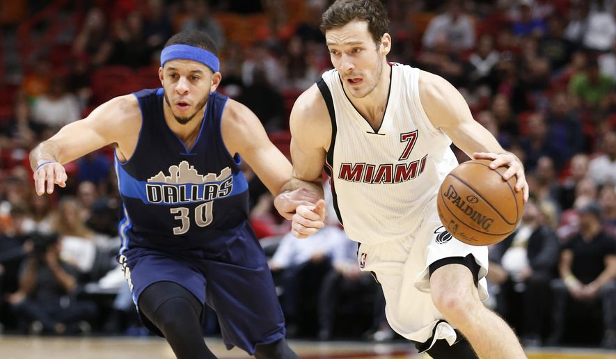 Miami Heat guard Goran Dragic (7) drives to the basket past Dallas Mavericks guard Seth Curry (30) during the second half of an NBA basketball game, Thursday, Jan. 19, 2017, in Miami. Dragic had 32 points as the Heat defeated the Mavericks 99-95. (AP Photo/Wilfredo Lee)