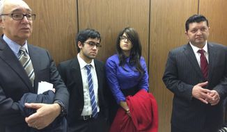 Crystal Crespo, second from right, and her brother, Daniel Nicholas Crespo, second from left, listen as the lawyers for their mother speak in a hallway of Los Angeles Superior Court in Los Angeles on Friday, Jan. 20, 2017. Lyvette Crespo was sentenced to three months in jail for the 2014 killing of their father, Daniel Crespo, the mayor of the small suburb of Bell Gardens. (AP Photo/Brian Melley)