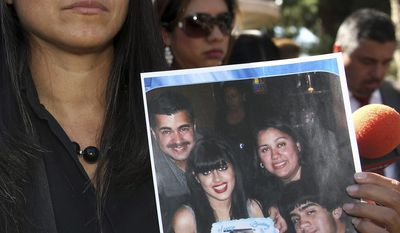 FILE - In this Oct. 2, 2014 file photo, attorney Claudia Osuna holds a photo of the Crespo family - from top left to bottom right, Bell Gardens, Calif., Mayor Daniel Crespo, his daughter Crystal, his wife Lyvette and son Daniel Crespo Jr. - during a news conference in Bell Gardens. Lyvette Crespo was sentenced Friday, Jan. 20, in Los Angeles Superior Court after pleading guilty to voluntary manslaughter in the 2014 killing of Bell Gardens Mayor Daniel Crespo. Crespo, She has been sentenced to three months in jail for killing him in their home. (AP Photo/Nick Ut, File)