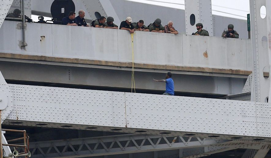 Sylvester Holt, bottom right, pleads with officers as while standing on the ledge of the Crescent City Connection Friday, Jan. 20, 2017, in New Orleans. Holt was wanted in the connection with the shooting of his wife and a Westwego police officer. (AP Photo/Jonathan Bachman)