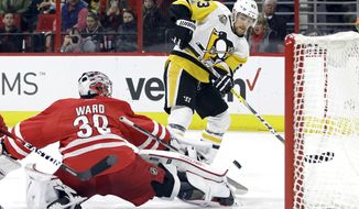 Pittsburgh Penguins' Scott Wilson (23) is blocked by Carolina Hurricanes goalie Cam Ward (30) during the first period of an NHL hockey game in Raleigh, N.C., Friday, Jan. 20, 2017. (AP Photo/Gerry Broome)