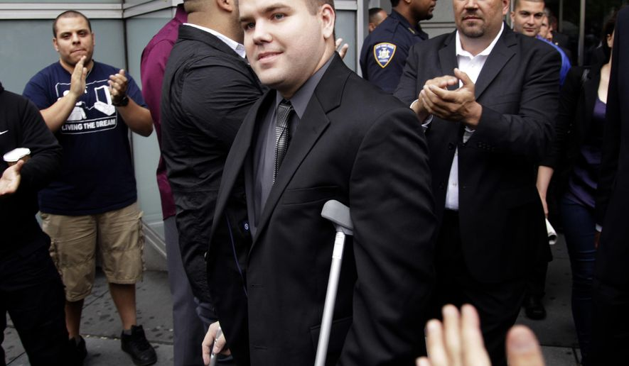 FILE - In this June 13, 2012, file photo, police officers and supporters clap as Officer Richard Haste, center, exits the courthouse after posting bail in New York. Haste pleaded not guilty to manslaughter charges in the shooting death of unarmed, black teenager Ramarley Graham. Haste was expected to offer his first public account of the slaying at his department disciplinary trial on Friday, Jan. 20, 2017. Haste initially faced a criminal manslaughter charge in the 2012 death of Graham, but the case was ultimately dismissed.  (AP Photo/Seth Wenig, File)