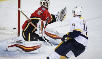 Nashville Predators' Ryan Ellis, right, scores on Calgary Flames goalie Chad Johnson during the second period of an NHL hockey game Thursday, Jan. 19, 2017, in Calgary, Alberta. (Jeff McIntosh/The Canadian Press via AP)