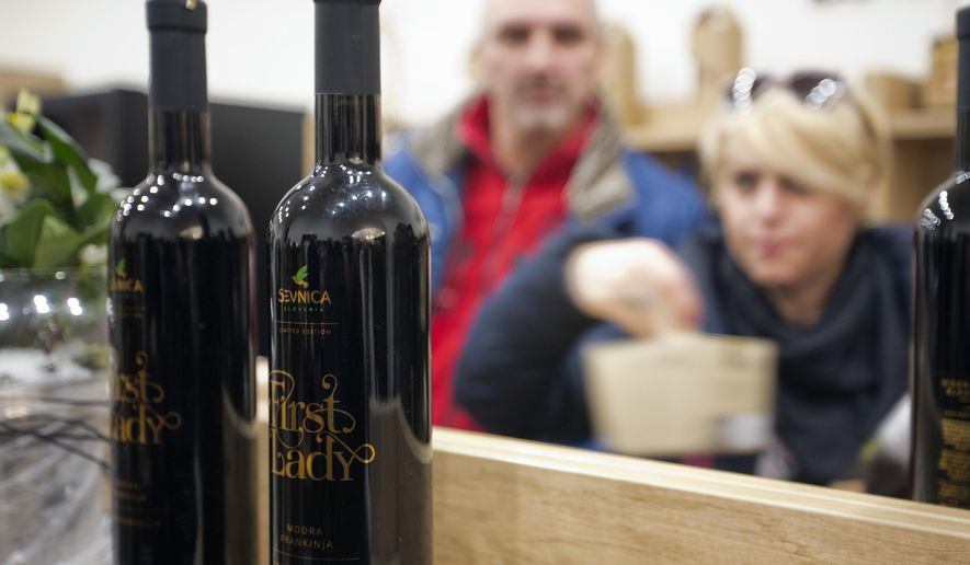 """Visitors look at bottles of local wine """"First Lady"""" displayed for visitors in Sevnica, Slovenia, Friday, Jan. 20, 2017. The inauguration of Donald Trump is a big thing for a small town in Slovenia where the future U.S. first lady traces her roots. Starting Friday, the industrial town of Sevnica plans three days of events to mark the inauguration and welcome all guests wishing to see where Melania Trump grew up. (AP Photo/Darko Bandic)"""