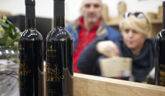 "Visitors look at bottles of local wine ""First Lady"" displayed for visitors in Sevnica, Slovenia, Friday, Jan. 20, 2017. The inauguration of Donald Trump is a big thing for a small town in Slovenia where the future U.S. first lady traces her roots. Starting Friday, the industrial town of Sevnica plans three days of events to mark the inauguration and welcome all guests wishing to see where Melania Trump grew up. (AP Photo/Darko Bandic)"