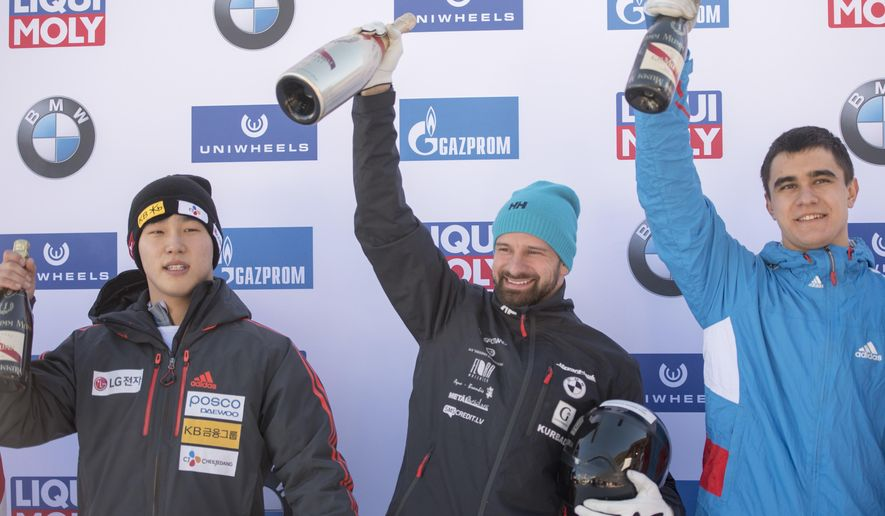 Second placed Yun Sung-bin from South Korea, winner Martins Dukurs from Latvia and third placed Nikita Tregybov from Russia celebrate after the men's skeleton World Cup in St. Moritz, Switzerland,  Friday, Jan. 20, 2017. (Urs Flueeler/Keystone via AP)