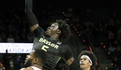 FILE - In this Jan. 17, 2017, file photo, Baylor forward Johnathan Motley (5) goes up for a shot over Texas' Shaquille Cleare (32) and Jarrett Allen (31) during an NCAA college basketball game in Waco, Texas. Motley is the leading scorer and rebounder for the Bears, who reached No. 1 for the first time this month.(AP Photo/Tony Gutierrez, File)