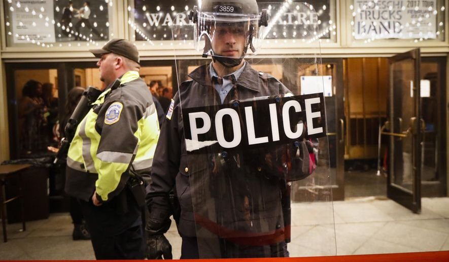 Police stand guard at the rope line outside of an presidential inauguration party at the Warner Theatre due to street protests, Thursday, Jan. 19, 2017, in Washington. (AP Photo/John Minchillo)